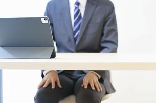 緊張した表情でオンライン面接・会議・打ち合わせに臨むスーツ姿の男性の写真素材 [FYI04915887]