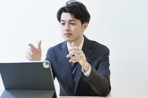 タブレットPCの画面に向かって話すスーツ姿の男性の写真素材 [FYI04915897]