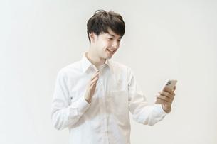 笑顔でスマートフォンに手を振る若い男性の写真素材 [FYI04915924]