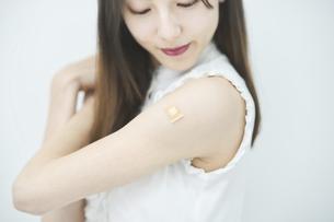 ワクチン接種のパッチが貼られた女性の腕の写真素材 [FYI04915934]