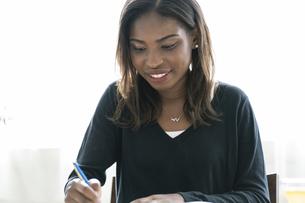 書き物をするアフリカ系外国人女性の写真素材 [FYI04916154]