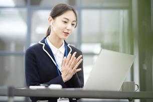 パソコンの画面に向かって話しかける女性の写真素材 [FYI04916370]