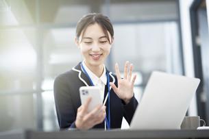 スマートフォンの画面に向かって話しかける若いビジネスウーマンの写真素材 [FYI04916451]