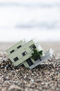砂に埋まる住宅模型の写真素材 [FYI04916639]