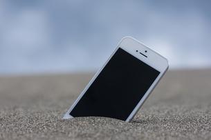 砂に埋まったスマートフォンの写真素材 [FYI04916644]