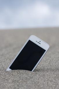 砂に埋まったスマートフォンの写真素材 [FYI04916645]