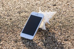砂浜に置かれたスマートフォンの写真素材 [FYI04916655]