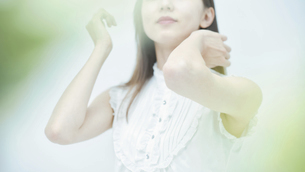 リラックスした表情で髪に触る若い女性の写真素材 [FYI04916772]