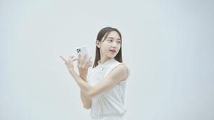 スマートフォンを持ちながら舞う若い女性の写真素材 [FYI04917000]