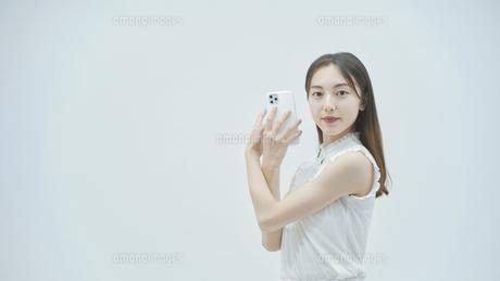 スマートフォンを持ちながら舞う若い女性の写真素材 [FYI04917001]