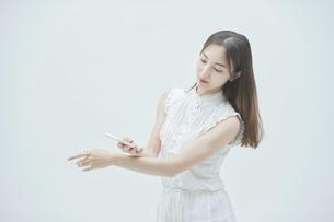 スマートフォンを持ちながら舞う若い女性の写真素材 [FYI04917002]