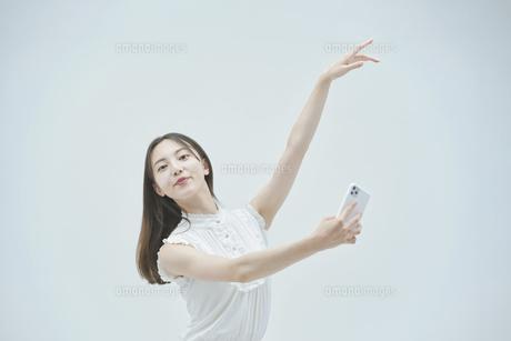 スマートフォンを持ちながら舞う若い女性の写真素材 [FYI04917003]