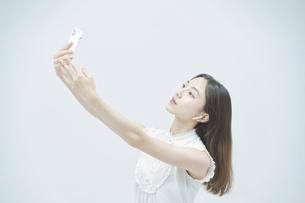 スマートフォンを持ちながら舞う若い女性の写真素材 [FYI04917004]