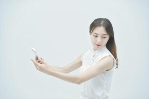 スマートフォンを持ちながら舞う若い女性の写真素材 [FYI04917005]