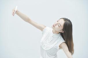 スマートフォンを持ちながら舞う若い女性の写真素材 [FYI04917006]