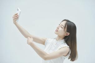 スマートフォンを持ちながら舞う若い女性の写真素材 [FYI04917015]