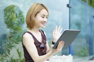 タブレットPCを使って、オンラインでコミュニケーションをする女性の写真素材 [FYI04917065]