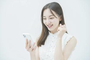 スマートフォンの画面を見ながらガッツポーズをする女性の写真素材 [FYI04917986]
