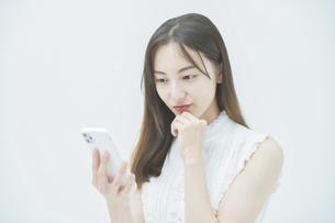 嫌な感情でスマートフォンを見る女性の写真素材 [FYI04918004]