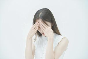 ストレスを抱えた表情をする若い女性の写真素材 [FYI04918011]