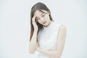 ストレスを抱えた表情をする若い女性の写真素材 [FYI04918014]