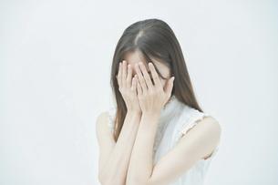 ストレスを抱えた表情をする若い女性の写真素材 [FYI04918017]