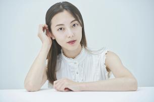 肘をつくポーズをする若い女性の写真素材 [FYI04918026]