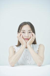 肘をつくポーズをする若い女性の写真素材 [FYI04918029]