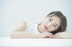 白いテーブルにもたれかかるポーズをする若い女性の写真素材 [FYI04918032]