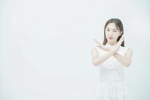 両手でバツのハンドサインをする若い女性の写真素材 [FYI04918034]