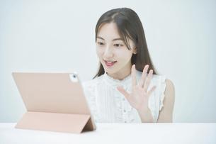 タブレットPCを使って、オンラインでコミュニケーションをする女性の写真素材 [FYI04918035]