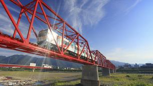 朝の赤い鉄橋を渡る輝くれいんどりーむ号の写真素材 [FYI04918384]