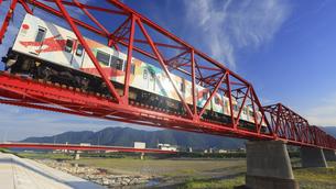 朝の赤い鉄橋を渡る輝くれいんどりーむ号の写真素材 [FYI04918386]