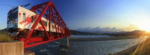 夕方の赤い鉄橋を渡る輝くれいんどりーむ号の写真素材 [FYI04918393]