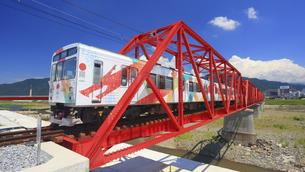 赤い鉄橋を渡るれいんどりーむ号のアップの写真素材 [FYI04918432]