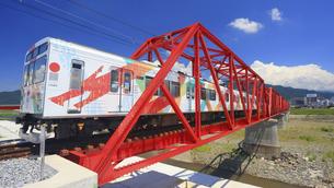 赤い鉄橋を渡るれいんどりーむ号のアップの写真素材 [FYI04918436]