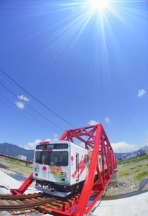 赤い鉄橋を渡るれいんどりーむ号のアップと太陽の光の写真素材 [FYI04918455]