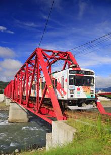 赤い鉄橋を渡るれいんどりーむ号のアップの写真素材 [FYI04918491]