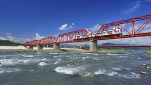 赤い鉄橋を渡るれいんどりーむ号と千曲川の清流の写真素材 [FYI04918495]