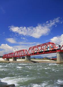 赤い鉄橋を渡るれいんどりーむ号と千曲川の清流の写真素材 [FYI04918496]