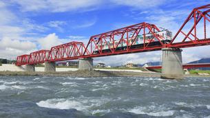 赤い鉄橋を渡るれいんどりーむ号と千曲川の清流の写真素材 [FYI04918501]
