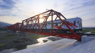 朝の赤い鉄橋を渡るれいんどりーむ号の写真素材 [FYI04918549]