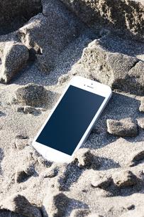 砂浜に置かれたスマートフォンの写真素材 [FYI04919963]