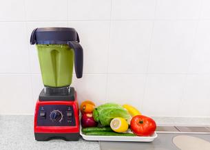 キッチンカウンターの上に置かれたミキサーの中のグリーンスムージー、さまざまな野菜とフルーツの写真素材 [FYI04920395]