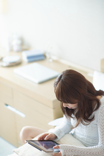 タブレットを操作する日本人女性の写真素材 [FYI04921993]