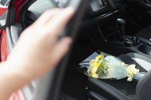車の助手席に置かれた花束とドアに置かれた手の写真素材 [FYI04922031]