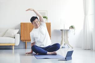タブレット端末を見ながら自宅でトレーニングをする若い男性の写真素材 [FYI04922318]