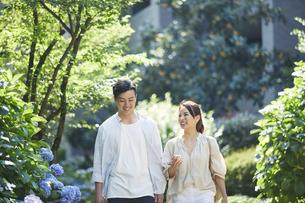 緑の中を歩く若い男性と女性の写真素材 [FYI04922319]