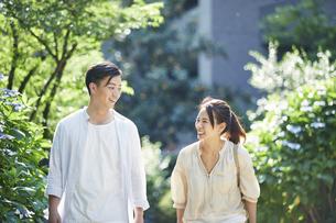 緑の中を歩く若い男性と女性の写真素材 [FYI04922325]
