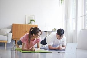 ノートパソコンを見ながら自宅でトレーニングをする若い男性と女性の写真素材 [FYI04922331]